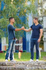 Two young men meeting in front of the college building