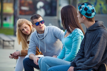 Group of four young people hanging out outdoors
