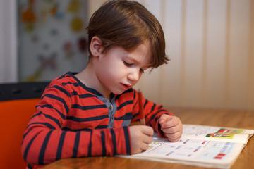 Little boy write maths exercise