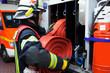 Feuerwehrmann in der Feuerwehrwache mit Wasserschlauch - 82447389