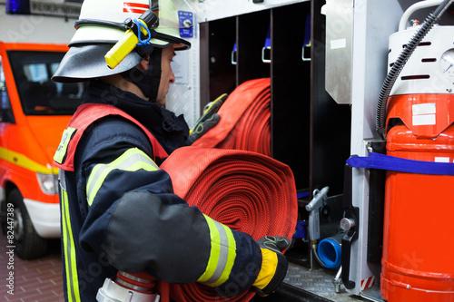 Feuerwehrmann in der Feuerwehrwache mit Wasserschlauch
