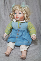 Vintage porcelain doll blonde on gray fabric background