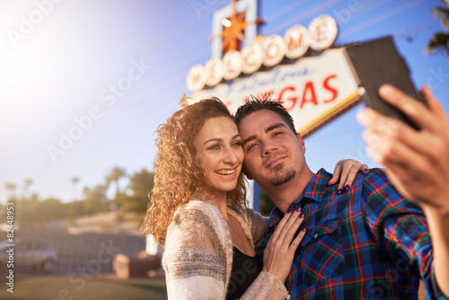 Poster romantic couple taking selfie by las vegas sign