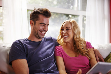 happy couple using table on couch together