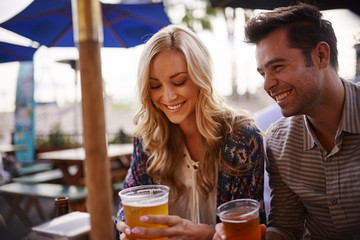 couple drinking beer at outdoor bar