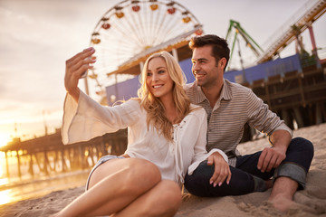 romantic couple taking selfie at sonica monica laying in sand
