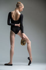 Portrait of the young fragile ballerina with an iron bronze mask