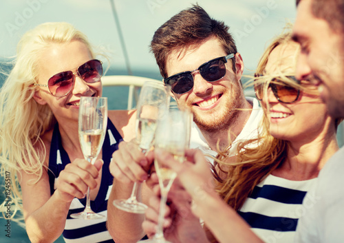smiling friends with glasses of champagne on yacht - 82455117