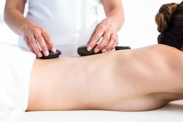 Brunette getting hot stone massage