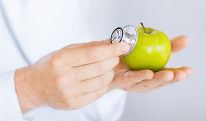 male doctor with green apple and stethoscope