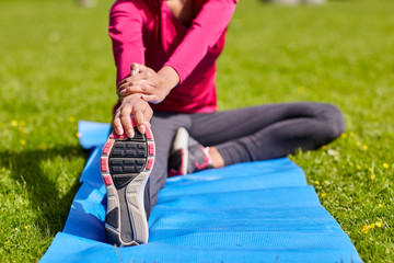 close up of woman stretching leg on mat outdoors