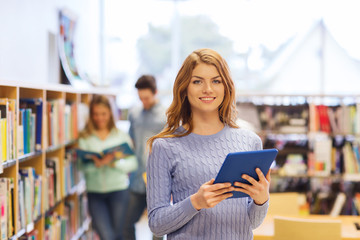 happy student girl with tablet pc in library