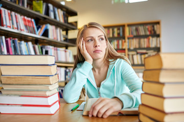 bored student or young woman with books in library