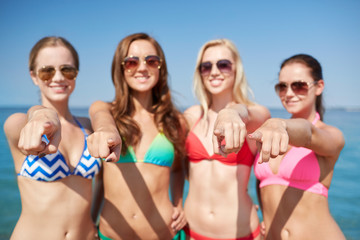 group of happy women pointing at you on beach