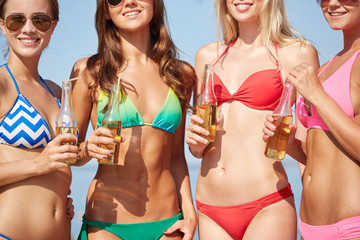 close up of young women drinking lemonade on beach