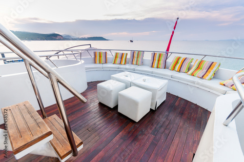 White stools and long seat on the yacht deck - 82458572