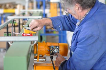 älterer Arbeitnehmer montiert Elektrik im Maschinenbau