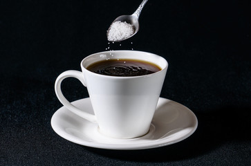 Sprinkling of sugar in a white cup of coffee