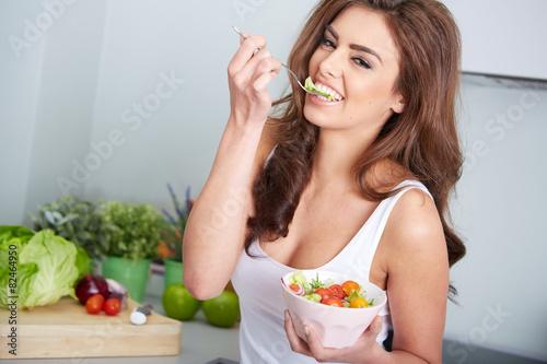 Leinwandbild Motiv junge frau isst einen salat