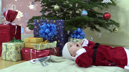 Lovely baby girl lie near christmas tree and gift present boxes