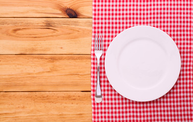 Empty plates, cutlery tablecloth on wooden table for dinner,