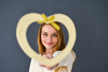 Closeup portrait of young female holding heart shape