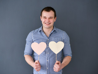 Young man holding two hearts. Valentine's Day.