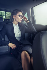 Young businesswoman in back seat of car