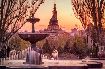 Fountain at sunset with church