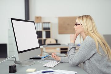 kreative junge frau am arbeitsplatz schaut auf bildschirm