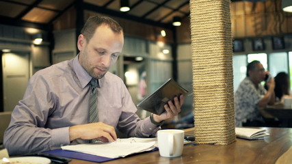 Businessman comparing data on tablet and documents in cafe