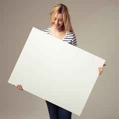 junge frau zeigt ein weißes plakat