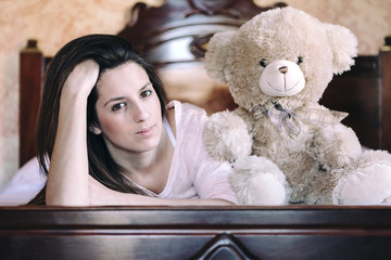 Happy woman lying in bed with her teddy bear at home