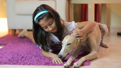 Happy little girl petting her dog at home