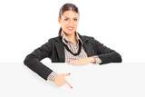 Young businesswoman pointing on a blank panel