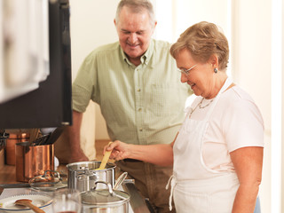 senior couple together in kitchen cooking pasta