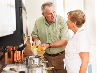 senior couple cooking pasta in kitchen at home