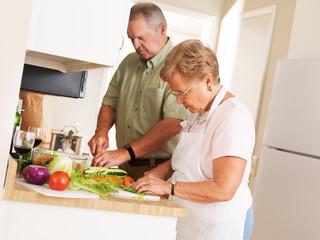 elderly senior couple at home preparing vegetables for a meal