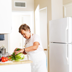 elderly woman in kitchen cutting vegetables