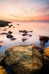Sunrise at mossy rock near ocean with milky looking water