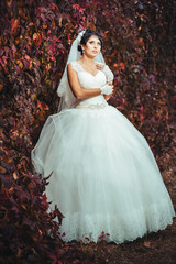 portrait of beautiful young bride holding bright bouquet in