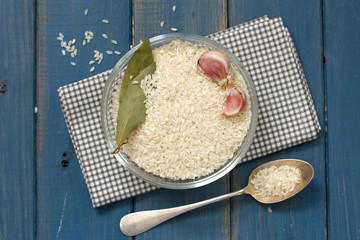 rice in bowl and spoon on blue background