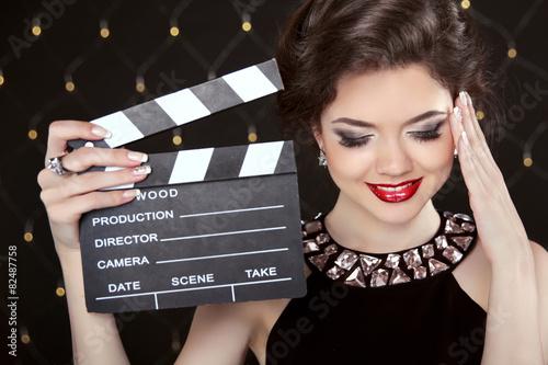 Fototapeta Fashion elegant woman posing with sexy red lips holding cinema c