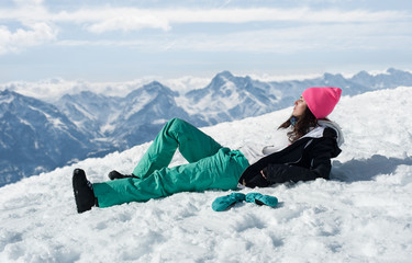 Women at mountains in winter lies on snow