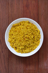couscous in white bowl on brown background