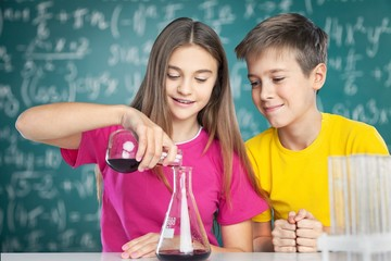 Project. Young school kids doing a chemistry experiment with the