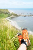 Relaxing with legs crossed and Kaikoura shore in the background