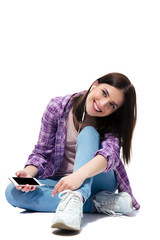 Happy young girl sitting on the floor with smartphone
