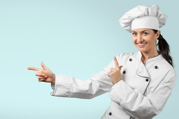 Chef. Cute female chef pointing to copy space