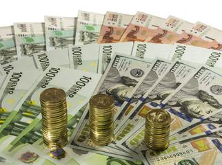 Стопки 10 рублевых монет на фоне купюр.